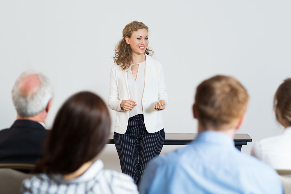 Woman giving a speech to a group of colleagues